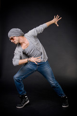 cool looking dancer posing on a grunge black wall
