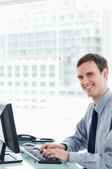 Side view of a happy office worker using a monitor