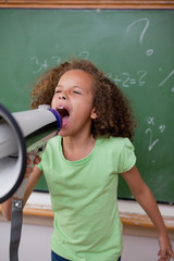 Portrait of a cute schoolgirl screaming through a megaphone