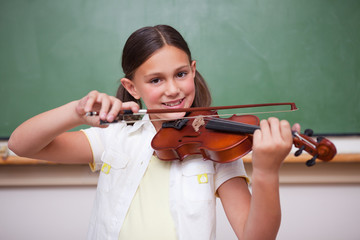Smiling schoolgirl playing the violin