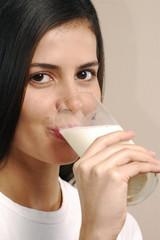 Joven mujer bebiendo leche.