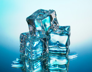 Melting ice cubes on blue background