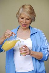 Señora bebiendo jugo de naranja.