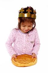enfant avec galette des rois dans les mains et couronne