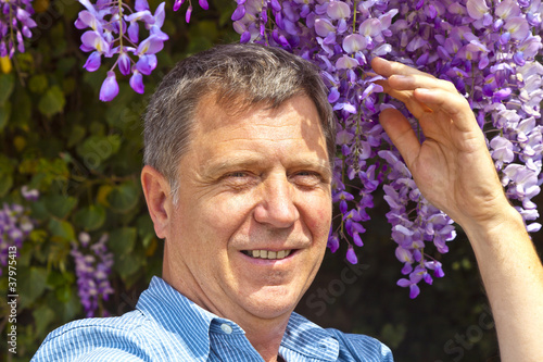 attractive man is smelling park flowers