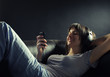 Relaxed smiling woman lying on sofa while listening music in hea