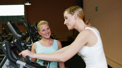 Fitness trainer with woman in gym