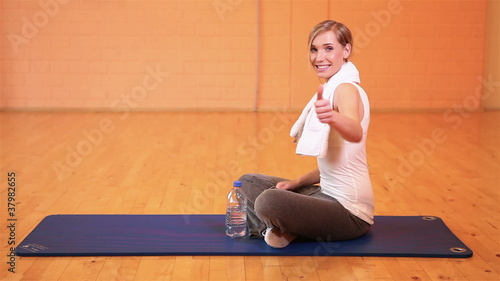 Exhausted woman in gym holding thumbs up