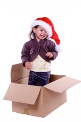 petite fille debout dans un carton avec chapeau de noel