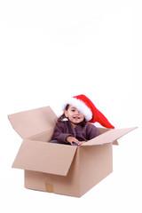 enfant assise dans un carton d'emballage a noël