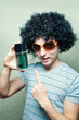 Funny guy in wig and eyeglasses with perfume bottle