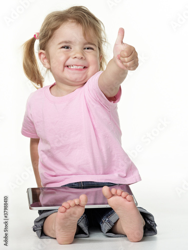 Adorable little girl on the floor playing with touchpad