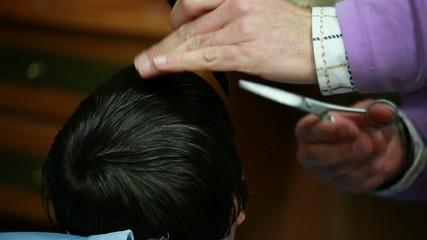 A child having a haircut with scissors