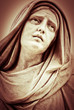 Vintage sepia image of a suffering religious woman statue