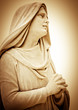Vintage sepia image of a suffering religious woman praying