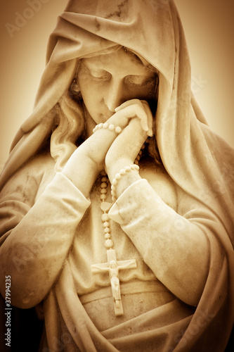 Vintage sepia image of a religious woman with a crucifix