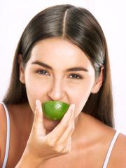 Joven mujer hispana sujetando y comiendo limón.
