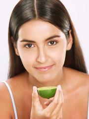 Joven mujer hispana sujetando limón.