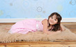 sweet little girl playfully posing on furry brown rug