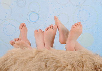children's feet over furry blanket
