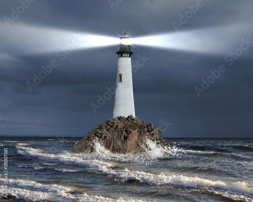 Leinwanddruck Bild Lighthouse with a beam of light