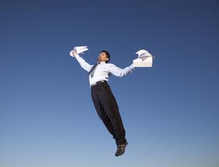 Businessman jump holding documents