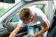 Mann saugt das Auto aus