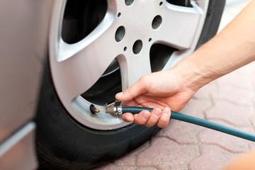 Mann prüft den Reifendruck seines Autos