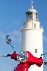 Detail of a red scooter and lighthouse on the background.