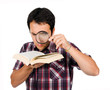 Young man reading a interesting book with magnifying glass, isol