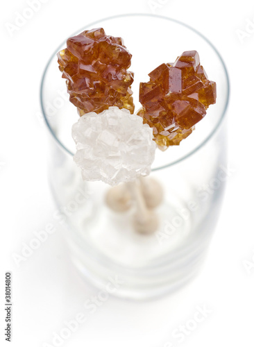 Candy brown and white sugar on a sticks in glass.