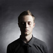 Portrait of a young stylish man against black background