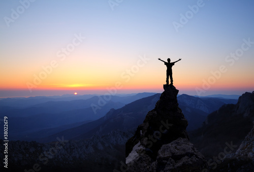 Silhouette of men on top of the mountain