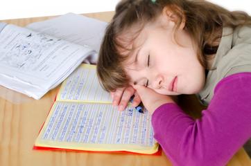 Mädchen schläft über Hausaufgaben