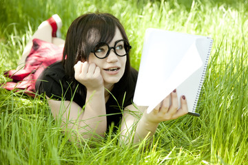 Young teen girl with notebook at green grass.