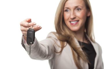 Frau überreicht Autoschlüssel
