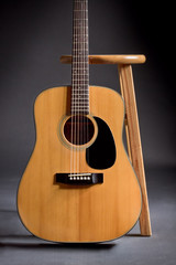 Acoustic guitar leaning against a wooden stool