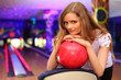 thoughtful girl stands and bases on red ball in bowling club