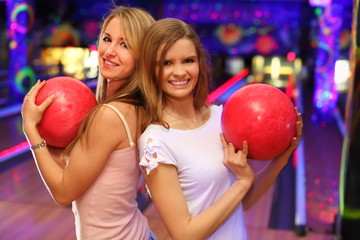 Two girls wearing white T-shirts stand and keep red ball