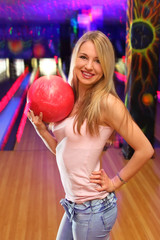 beautiful girl stands and keeps in hand ball in bowling club
