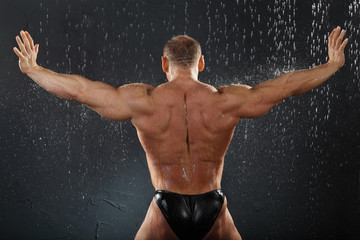 Undressed bodybuilder stands in rain back to camera