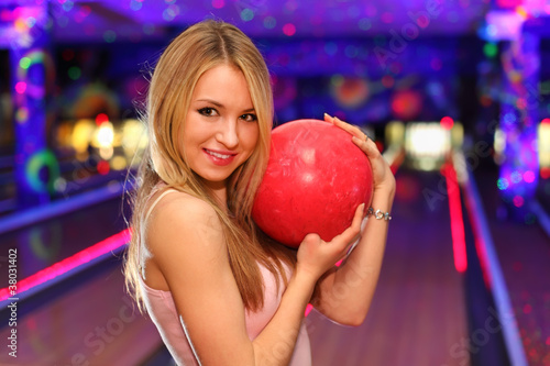 blonde girl stands and hugs red ball in bowling club