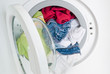 washing machine door full of colored clothes