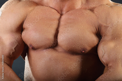 Strong chest and hand muscles of undressed wet bodybuilders