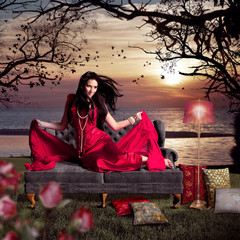 schöne Frau im roten Abendkleid auf antikem Sofa am Seeufer / l