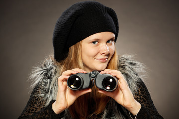 Teenager girl in winter clothing looking through binoculars