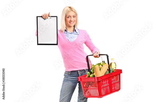 A female holding a shopping basket and showing a clipboard