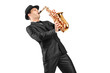 A man in a suit playing on saxophone
