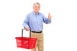A mature man holding an empty shopping basket and giving thumb u