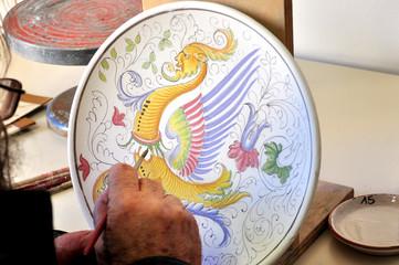 Decorazione a mano di un piatto di ceramica, Deruta Italia